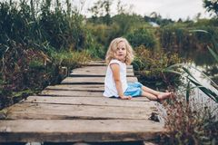 girl sitting on a wooden pier Stock Images
