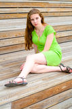 Girl sitting on wooden stairs Stock Images
