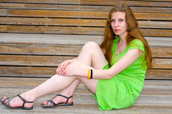 Girl sitting on wooden stairs Royalty Free Stock Image