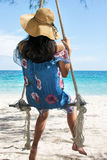 Girl sitting on a wooden swing on the beach Stock Photos