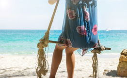 Girl sitting on a wooden swing on the beach Stock Images