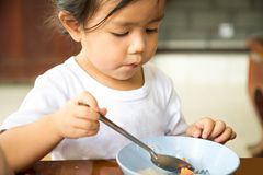 Girl is sitting at the wooden table for eat noodle that in the b Royalty Free Stock Photography