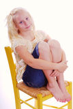 Girl Sitting in Yellow Chair Hugging her legs. Young Blonde Girl Sitting in a Yellow wooden chair with her arms wrapped around her hugging her knees on the seat Royalty Free Stock Image