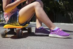 A girl is sitting on a yellow penny board. stock photos