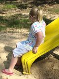 GIRL PLAYING ON YELLOW SLIDE  Royalty Free Stock Photos