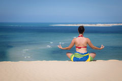 Girl in a sitting yoga pose in the beach Royalty Free Stock Photos