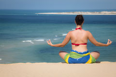 Girl in a sitting yoga pose in the beach Royalty Free Stock Photo