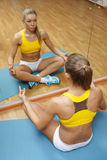 Girl sitting in yoga pose on floor mat in gym Stock Image