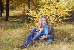 Girl  sittingt on grass in autumn forest. Royalty Free Stock Photo