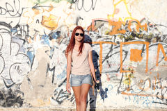 Girl with skateboard on background of graffiti Stock Photos