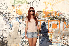 Girl with skateboard on background wall of graffiti Royalty Free Stock Photo