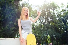 Girl with skateboard making selfie photo Royalty Free Stock Images