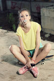 The girl on a skateboard. Modern hipster girl sitting on a skateboard and inflates gum Stock Photography