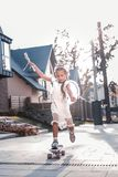 Modern little girl wearing little crown skateboarding near her house royalty free stock image