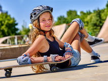 Girl with skateboard at the skate park. Teen girl in helmet sitting on his skateboard outdoor. Fall on person . Girl lying on a skateboard in a skate park Royalty Free Stock Photography