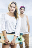 Girl with a skateboard stands in front of a boy Stock Photography