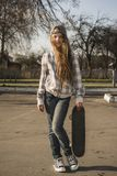Girl with skateboard on street Royalty Free Stock Images