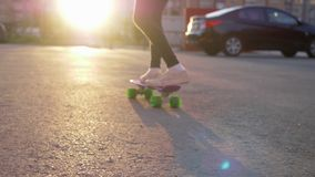 Girl skateboard urban scenery child foot back view. Kid ride city asphalt road schoolgirl pastime leisure activity. Teenager have fun healthy lifestyle sunset stock video footage