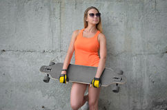 Girl on skateboard. Young and beautiful girl stands with her skateboard near the concrete wall Stock Photography