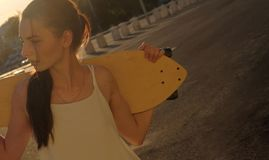 Girl with skatedoard behind her shoulders in summer looking away Royalty Free Stock Photography