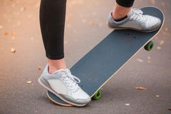 Girl skater raises the front of the skateboard close up stock photo
