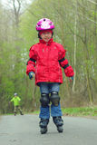 Girl skates outdoor inline skating. Young girl learning to skate on inline skates Royalty Free Stock Images