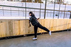 Girl skates at the rink in the winter time Stock Image