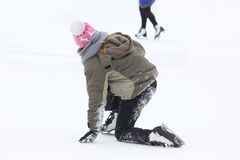 Girl on the skates rises after a fall on the ice rink