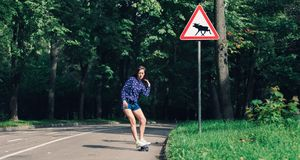 Girl skating penny board in the middle of asphalt road in the park royalty free stock image