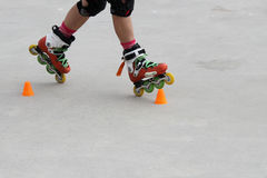 Girl skating in two wheels. With cones Stock Photography