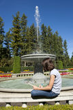 Girl sketches a fountain. A young girl sketches a water fountain on a sunny day Stock Photography