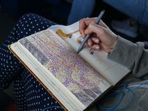 Girl sketching while commuting to work royalty free stock photography