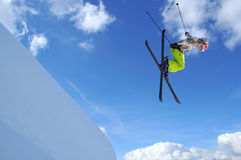 Girl ski jumper. Girl jumping with crossed skis over a steep cliff Stock Image