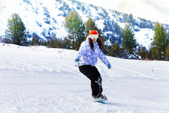 Girl in ski mask sliding with snowboard Stock Image