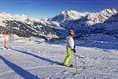 Girl on ski on the mountain slope in swiss alps jungfrau region. Near cabin car railway on ski resort Royalty Free Stock Image