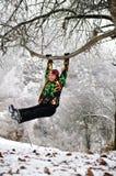 Girl in ski suit on tree in snowy winter Stock Photo