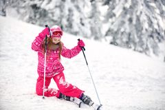 Girl on ski terrain practice to raise from snowy terrain Royalty Free Stock Images