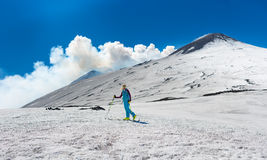 Girl ski touring under the top of the crater of Mount Etna stock photography