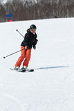 Girl skier coming down the ski from a mountain on a sunny day Stock Photos