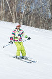 Girl skier coming down the slope on sunny day Stock Photography