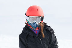 Girl skier portrait wrapped up warm in skiing gear with orange h Royalty Free Stock Images