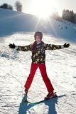 A girl skier in red pants and a green jacket on skis stretching out her arms happy with the sun`s rays Royalty Free Stock Photo