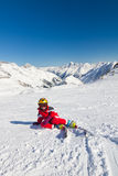 Girl skier sitting on a ski slope Stock Images