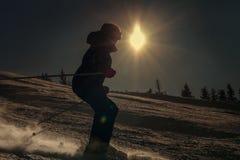 Girl skier skate down on snow hill in sun backlight Royalty Free Stock Image