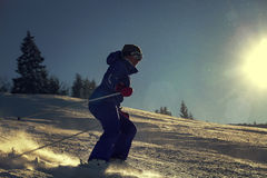 Girl skier slade down on the snow hill in bright sun backlight Stock Photography