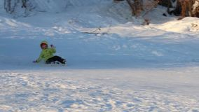 Girl skier slides down from hill and falls at winter day, two unrecognizable children are on hill stock video footage