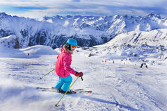 Girl skier in winter resort. Skiing, winter, child - portrait of young skier girl in helmet and goggles in winter resort Royalty Free Stock Image
