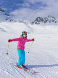 Girl skier in winter resort. Skiing, winter, child - portrait of young skier girl in helmet and goggles in winter resort Royalty Free Stock Photo