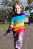 Girl skipping. A cute little girl in a colorful sweater skipping with her rope royalty free stock images