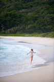 Girl skipping along the shore,seychelles. A girl skipping along the shore and splashing in the waves on the island of la digue in the seychelles Stock Photos